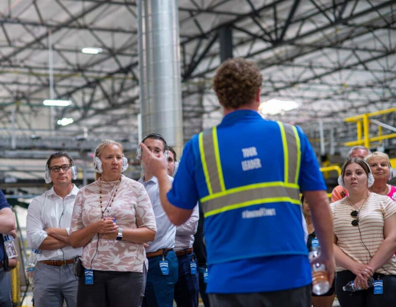 """A man wearing a safety vest marked """"TOUR LEADER"""" addresses a small group in a high-ceilinged space."""