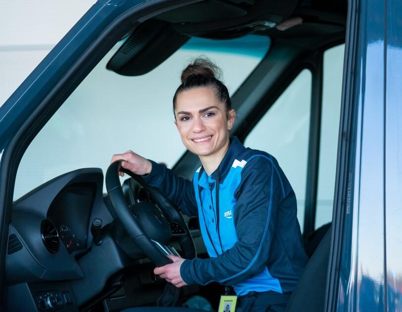 Eine junge Frau in blauer  Amazon Lieferuniform sitzt am Steuer eines Lieferwagens, sie blickt lächelnd in die Kamera.
