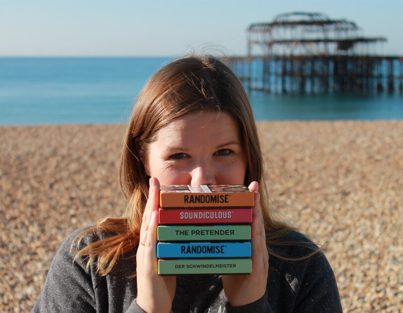 Hazel Reynolds, Founder of Gamely Games, standing in a beach holding all of her games.