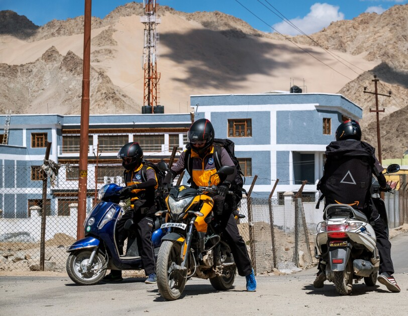On a dirt road, one man sits on a motorcycle, and two men sit on motor scooters. All three men wear helmets, backpacks, and uniforms. They appear to be preparing to ride away.