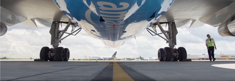 Ein Mitarbeiter läuft unter dem Flügel eines Amazon Prime Fliegers auf der Startbahn.