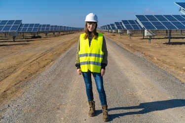 Eine dunkelhaarige Frau mit gelber Warnweste steht vor einem Solarpark. Sie lächelt in die Kamera. Hinter ihr sieht man die Solarpanels.