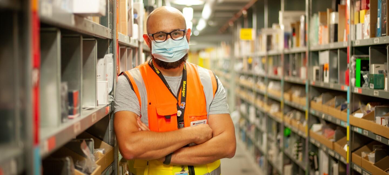Ein lächelnder Mitarbeiter mit Maske in einem Lagergang.