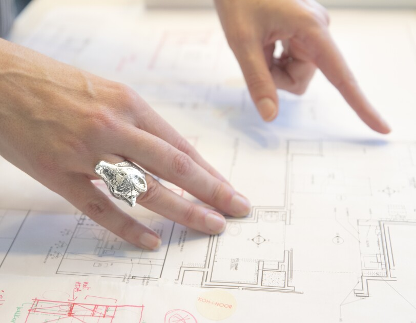 A woman's hands, with a large silver giraffe ring, points to architectural design plans.
