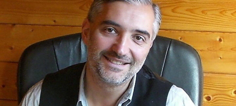 Portrait resserré de Laurent Bettoni, assis sur un fauteur en cuir devant une paroi en bois