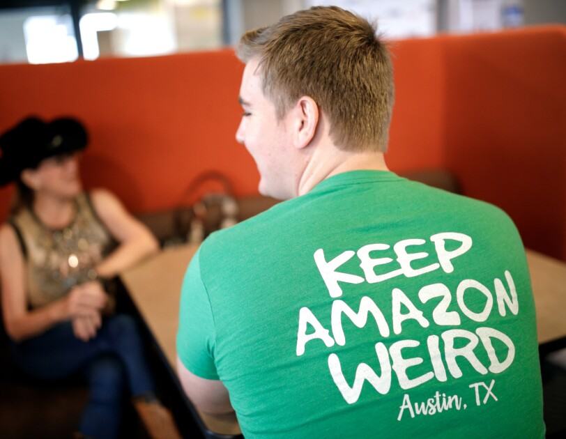 """An Amazonian sits, facing away from the camera, in the Austin, TX Amazon office. The back of his shirt says """"Keep Amazon weird - Austin, TX."""" Across the table sits another person, wearing a tank top, jeans, and brimmed hat."""