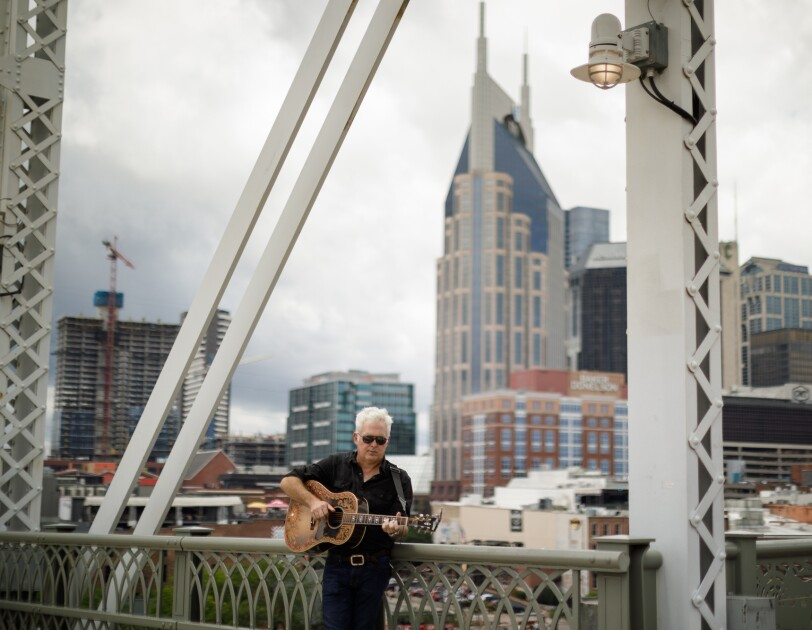 A man stands on a large metal bridge and plays an acoustic guitar with a city skyline behind him.