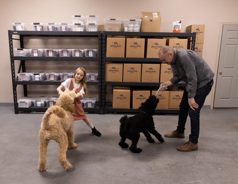 In a storeroom setting, a girl and a man play with two dogs.