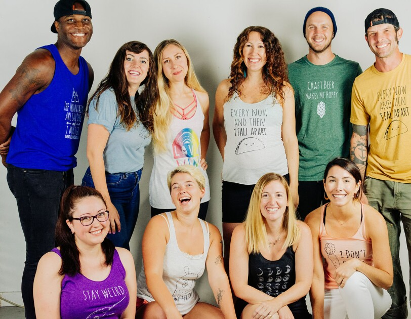 Ten young adults gather together for a posed photograph, smiling at the camera.