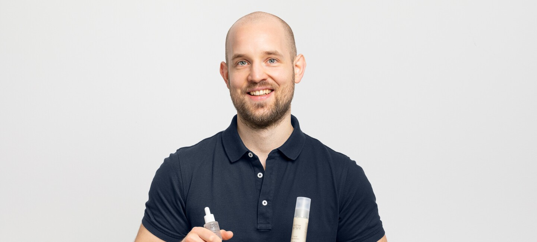 Ein Mann mit Glatze und einem schwarzen Poloshirt lacht in die Kamera. In seinen Händen hält er Produkte von Mellow Noir.
