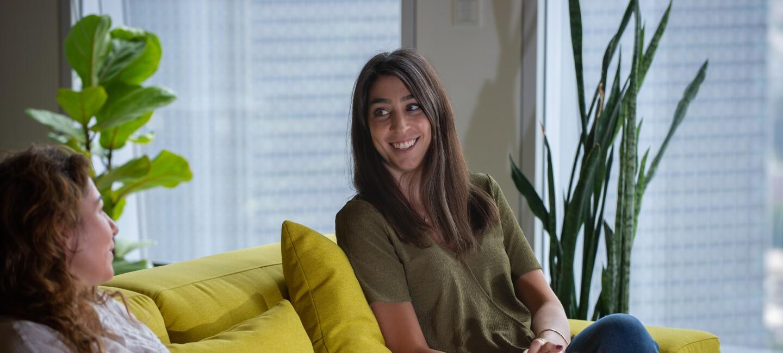 Amazon employee sat on yellow sofa talking with colleague