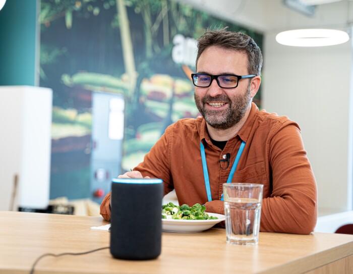 Daniel Méndez, Content Program Manager de Alexa comiendo una ensalada y con un vaso de agua en una mesa. Enfrente de un altavoz inteligente Amazon Echo.