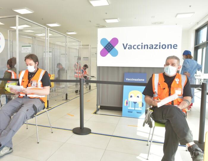 Due dipendenti Amazon attendono il loro turno per ricevere il vaccino contro il covid-19 in un'area dedicata di un sito Amazon. Sulla destra, alle spalle di uno dei due, si vede un cartellone bianco con la scritta 'Vaccinazione' e due cerotti colorati che si incrociano
