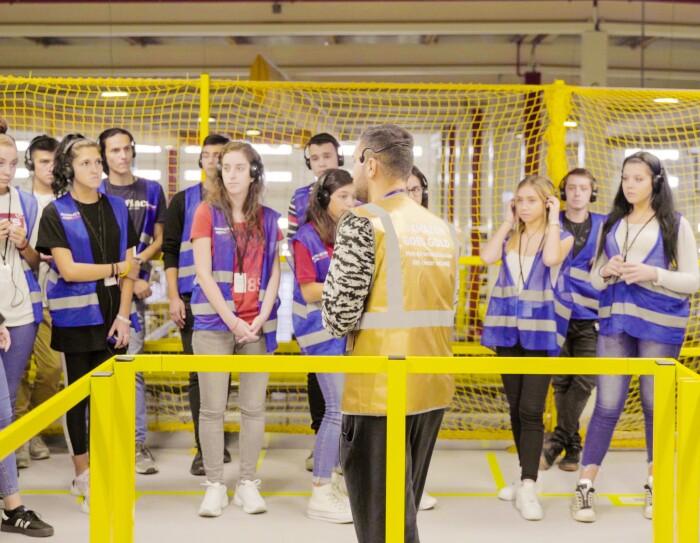 En un centro logístico con barandillas de color amarillo hay 16 adolescentes que participan en un FC Tour. Hay dos guías con chaleco dorado. Todos tienen auriculares con lo que escuchan la explicación del guía. Los adolescentes van con un chaleco azul.