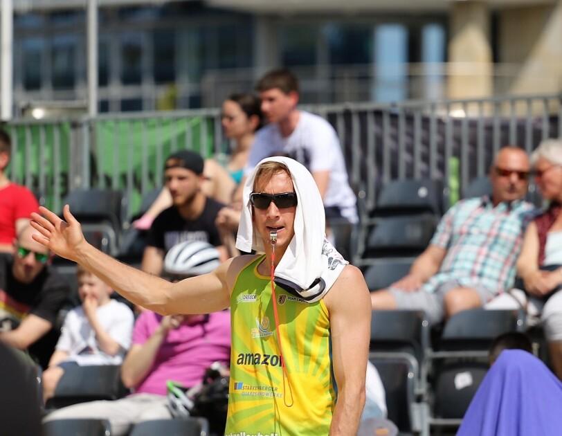 Ein Volleyballer im Amazon-Trikot hat eine Pfeife im Mund und hebt den Arm. Auf seinem Kopf liegt ein T-Shirt als Sonnenschutz