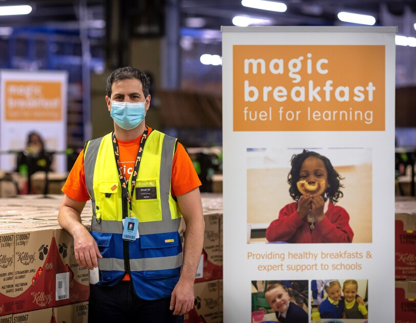 Amazon employee stood next to a Magic breakfast sign and cereal boxes