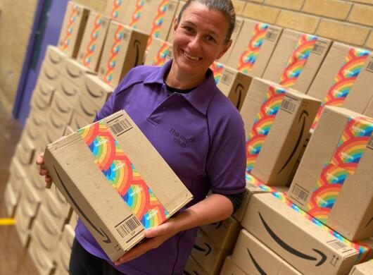 A person in a purple shirt smiles while holding an Amazon package with rainbow tape