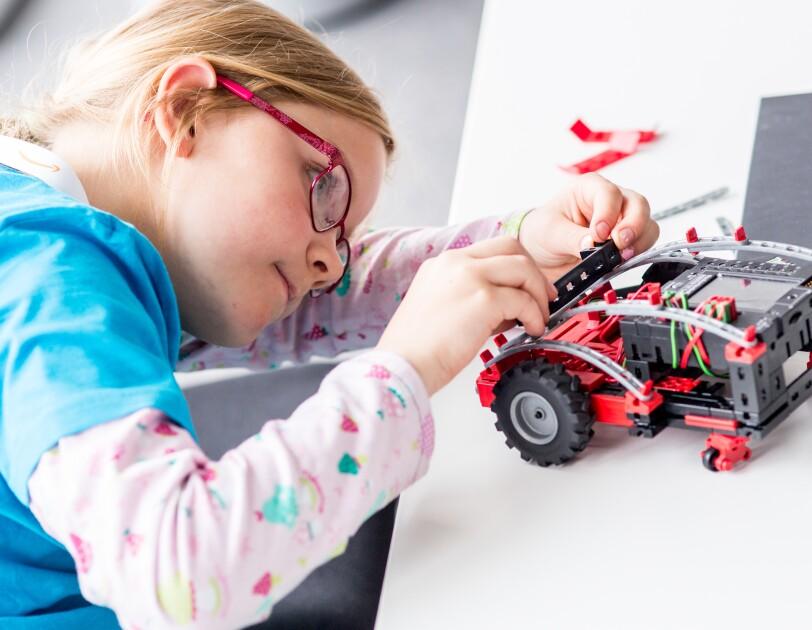 Ein kleines Mädchen mit Brille blickt auf einen mit Fischertechnik gebastelten Mini-Roboter, der auf einem Tisch steht