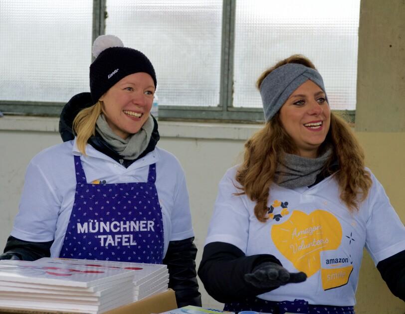 """Zwei Junge Frauen geben an der Großmarkthalle Weihnachtskalender aus. Eine trägt eine Schürze mit Aufschrift """"Münchner Tafel"""", die andere ein T-Shirt mit Aufdruck """"Amazon Volunteesrs"""""""