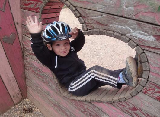 Ein kleiner Junge mit Fahrradhelm und Trainingshose