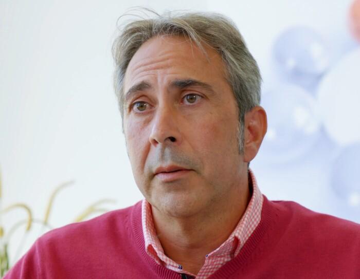 Francisco Ibáñez, socio fundador de Innovatec. Con el pelo blanco y los ojos verdes, lleva una camisa de cuadros blanca y rosa  y un jesey rosa. De fondo una pared blanca y una planta de color verde.
