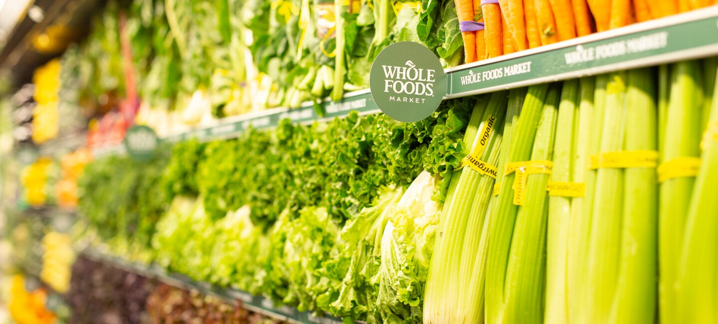 Photograph from within a Whole Foods Market showing fresh produce on display.