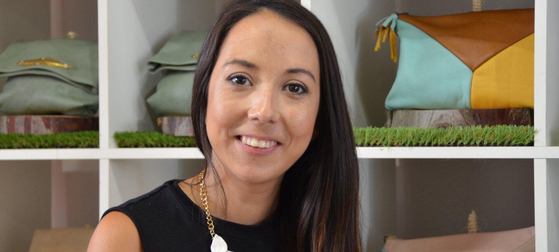 Lilian Urquieta es diseñadora. Posa con pelo largo y vestido negro delante de una estantería llena de los bosos que ella diseña.