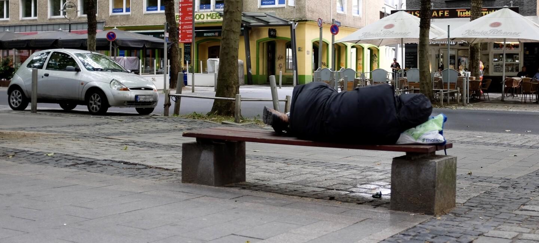 Ein obdachloser Mann ist von hinten auf einer Parkbank liegend zu sehen