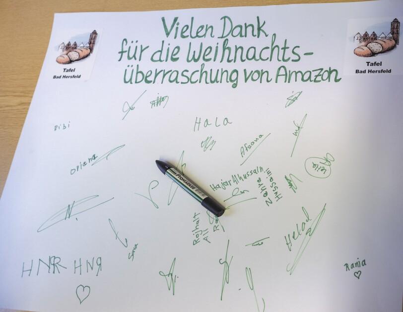 """Ein Dankesschreiben der Bad Hersfelder Tafel an Amazon: In grüner Schrift steht fett auf einem weißen Blatt Papier: """"Vielen Dank für die Weihnachtsüberraschung von Amazon"""". Darunter rund ein Dutzend Unterschriften."""