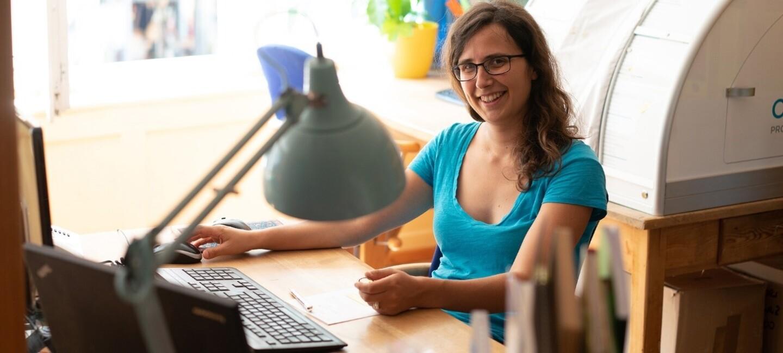Lena Ellensohn von Lindauer, Teilnehmerin von Unternehmerinnen der Zukunft, sitzt am Schreibtisch und lächelt in die Kamera.