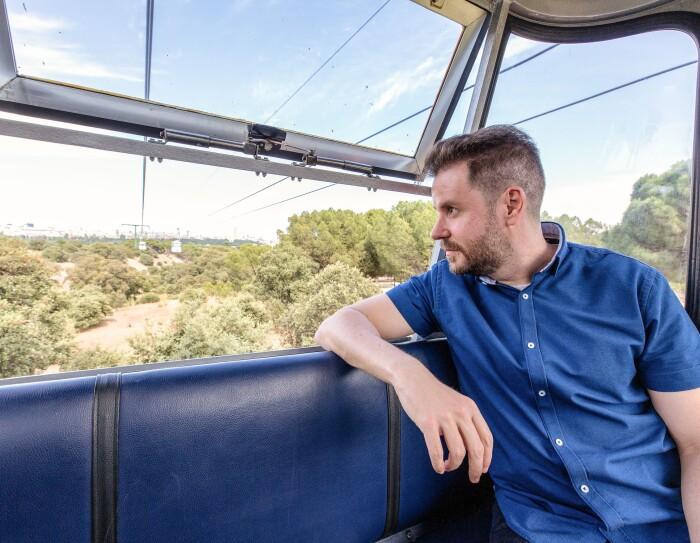 En el teleférico de Madrid, Paul Pen mirando al horizonte. La ventana de la cabina está abierta y  Paul tiene un brazo reposando en la silla. El escritor lleva una camisa azul y el pelo corto.