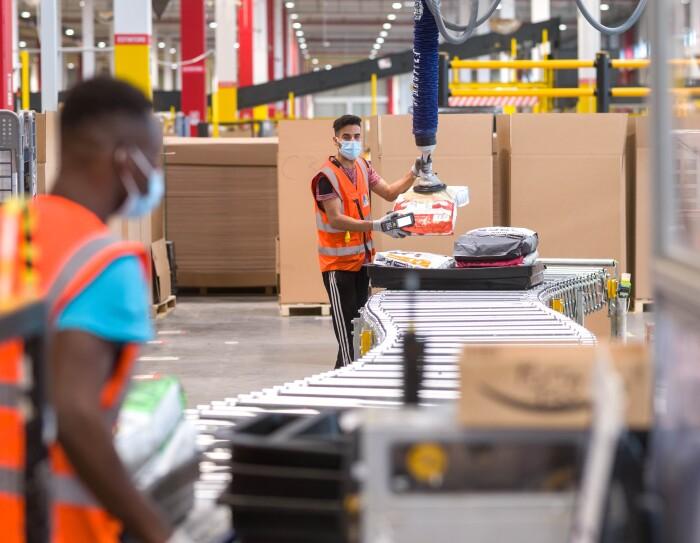 Due dipendenti Amazon agli estremi di un nastro trasporta-pacchi in un magazzino Amazon. Uno di loro è in primo piano, sfocato, sulla sinistra, è ripreso di spalle.