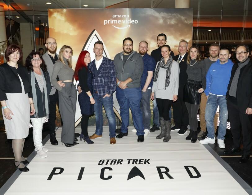 Eine Gruppe von Mitarbeitern vor der Fotoleinwand auf der Premiere: Zwischen ihnen in der Mitte das Star Trek Logo, im Hintergrund auf der Fotoleinwand ist das amazon prime video Logo erkennbar.
