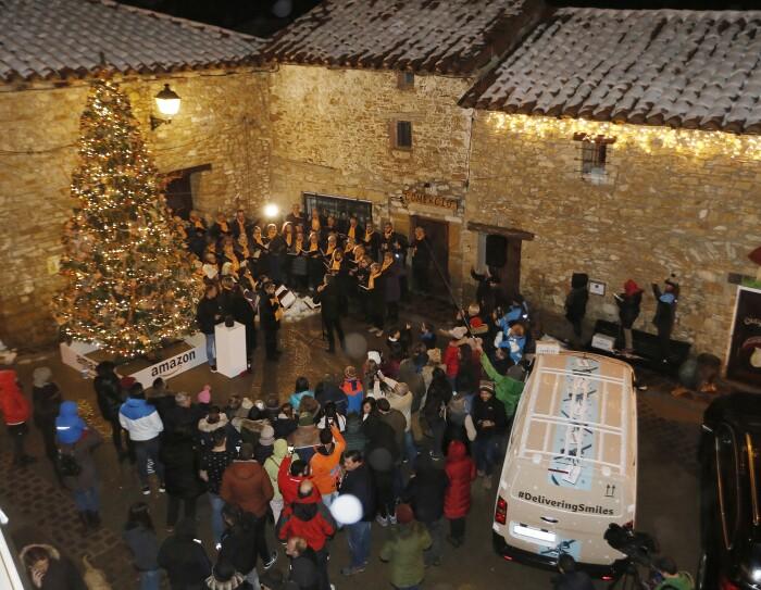 En la plaza principal de Valdelinares rodeada de tres casa de piedra con nieve en el tejado se encuentra: un árbol de Navidad decorado con luces y detrás un coor de 40 cantantes vestidos de negro y con una bufanda de color amarillo. Rodeando el árbil y el coro, los vecinos del pueblo.
