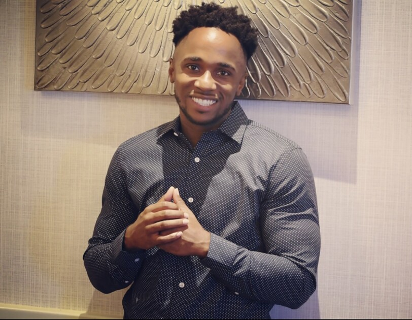 A Black man wearing a button up shirt smiles at the camera.
