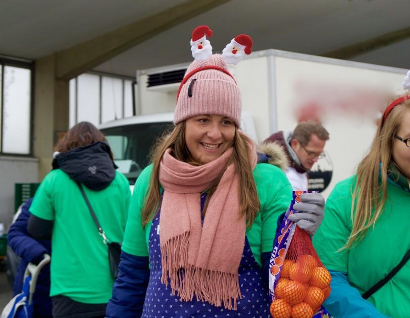 Eine junge Frau mit Wollmütze, Schal, grünem Shirt und blauer Schürze hält ein Netz mit Orangen. Über ihrer Wollmütze trägt sie einen Haarreif mit 2 Nikoläusen.