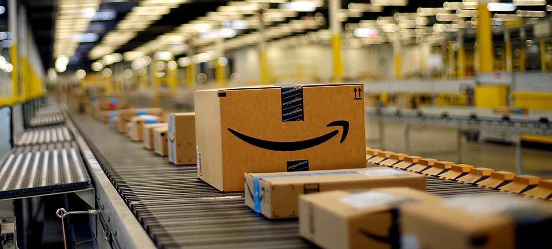 Pakete mit der Aufschirft Amazon fahren auf einem Paketband