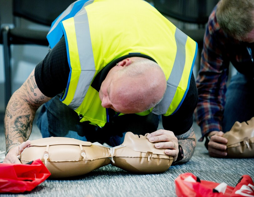 Amazon employee having CPR training with British Health Foundation using a CPR dummy. He is holding the dummy's nose and listening to the breathing.