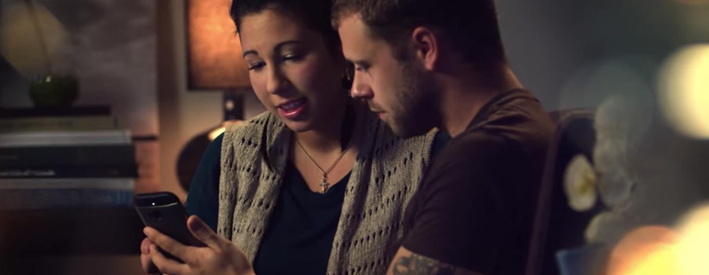 Un uomo e una donna guardano lo schermo di uno smartphone nella stanza di un'abitazione. L'uomo regge lo smartphone con il braccio sinistro. Alla sua destra, la donna gli indica lo schermo con la mano destra.