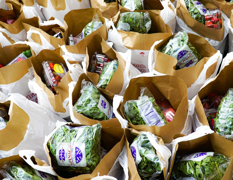 Overhead photograph of dozens of bags filled with fresh strawberries, spinach, and other groceries.