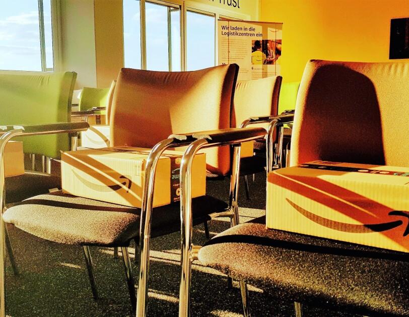 Ein lichtdurchfluteter Konferenzraum mit Stühlen: Auf jedem Platz liegt ein Amazon Päckchen. Gut sichbar: der Amazon Smile Pfeil