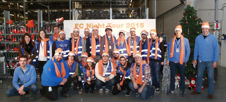 Foto de grupo de 23 personas posando delante de un cartel FC Night Tour 2015. Algunos de ellos lucen una bufanda de color naranja y un chaleco de color azul.