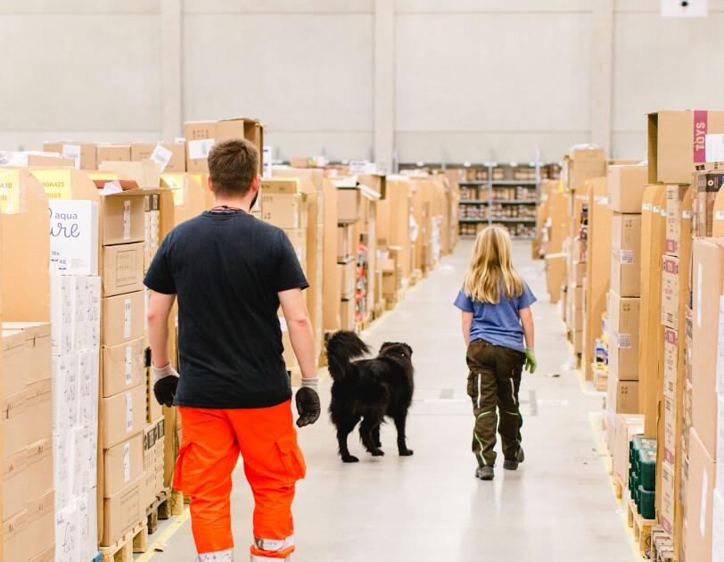 Ein Mädchen und ein Mitarbeiter der Rettungshundestaffel laufen durch den Palettengang eines Logistikzentrums, vor ihnen: ein schwarzhaariger Rettungshund.
