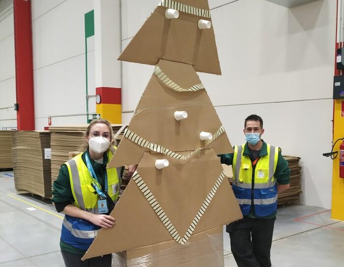 Adorno navideño de DMA8. Hay dos asociados con pantalón negro, chaleco amarillo y azul  y mascarilla. El árbol está hecho de cartón y mide casi tres metros.