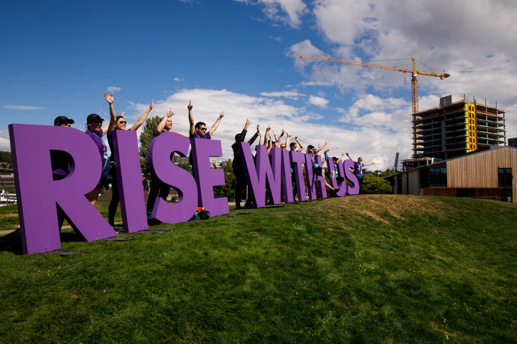"""Rise with us"" sign for the Special Olympics USA Games, set on a hillside in Seattle. The purple letters are shown with more than a dozen Amazon employee volunteers waving and smiling, as they welcome athletes to the closing ceremony."