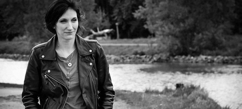 Amélie Antoine se promène dans la campagne en blouson de cuir, derrière elle se trouvent une rivière et des arbres. C'est une photo noir et blanc.