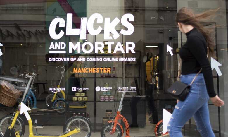 A lady walking past the first Clicks & mortar store in Manchester