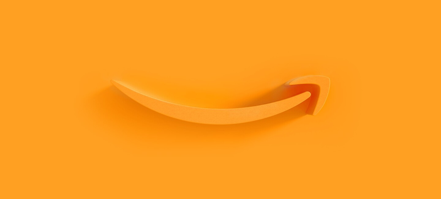 Amazon's orange smile logo appears as an extruded plastic form on an orange background, with a shadow cast by a light source from the right