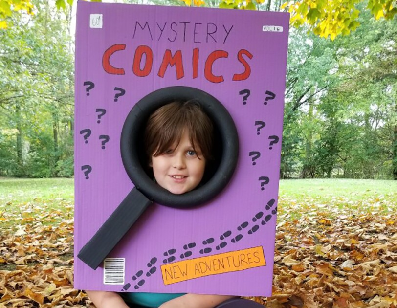 "A comic book Halloween costume created from a box that was painted purple. It says ""Mystery comics"" and ""new adventures,"" plus several question marks. The box is worn by a child, whose face peeks out from the center of a magnifying glass shape."