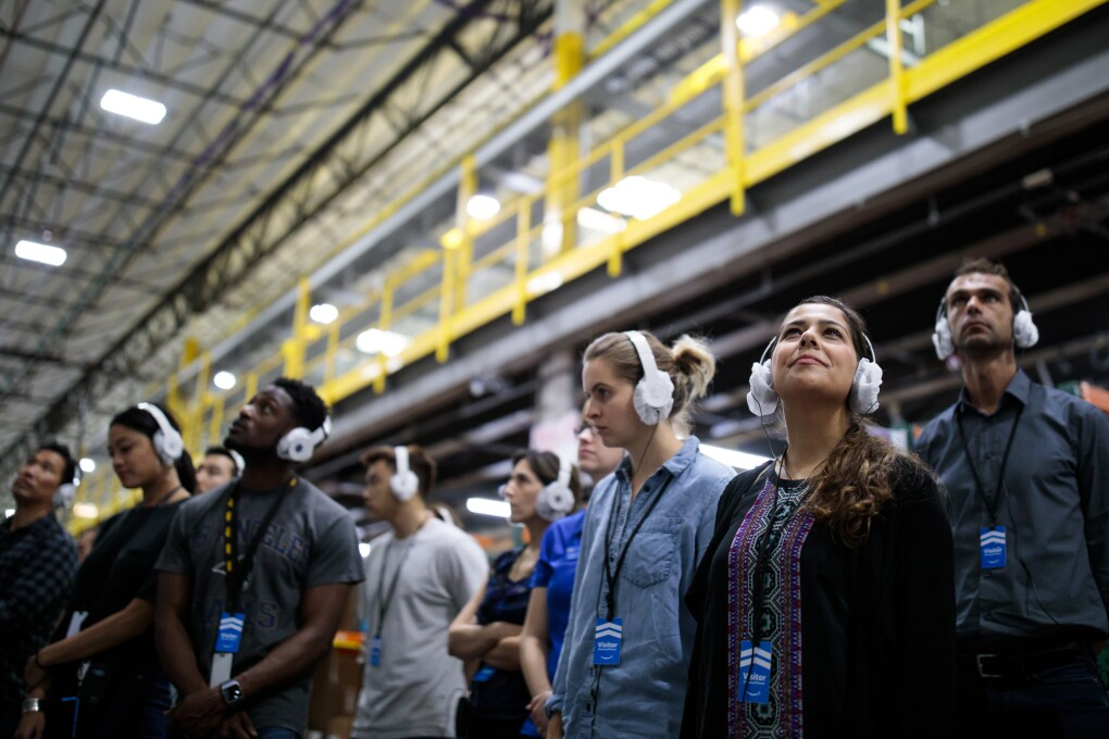 A group of people wearing earphones stand in a high-ceilinged space.